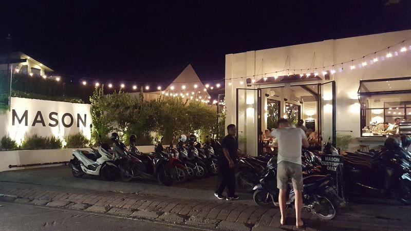 """Mason Canggu bei Nacht. Links auf einer Mauer der beleuchtete Schriftzug """"Mason"""", daneben der Parkplatz voll mit Mopeds und mit einer Lichterkette überspannt, dahinter ist das Restaurant zu sehen."""