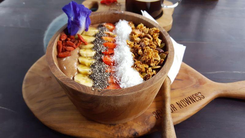 Mudra Café. Macchu Picchu Bowl. Smoothie Bowl aus rohem Kakao, Bananen, Datteln, Heidelbeeren, Avocado und Cashew-Milch. Streifen-Topping aus Gojibeeren, Bananen, Chiasamen, Erdbeeren, Kokosraspel und Granola. Dekoriert mit einer blauen Blüte.