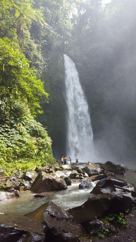 Nungnung Wasserfall. Im Vordergrund ein paar Felsen im Fluss dahinter der mächtige mindestens 20 Meter hohe Wasserfall.