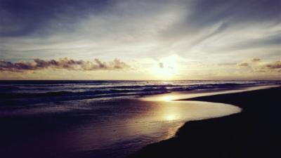 Sonnenuntergang am Strand von Canggu. Es ist schon sehr dunkel, die Sonne spiegelt sich im Ausläufer einer Welle, der Sand erscheint schwarz. Am Horizont ein paar Wolken, die wie ein Schleier über der Sonne liegen.