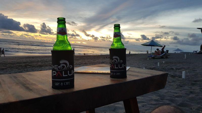 The Paluh Surf and Cafe. Sundowner. Im Vordergrund ein Tischchen mit zwei Flaschen Bier, dahinter der Sandstrand und am Horizont der Sonnenuntergang.