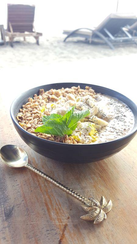 The Paluh Surf and Cafe. Smoothie Bowl auf einem Tischchen, daneben liegt ein Löffel mit einem Stielende in Form von Palmblättern. Im Hintergrund im Gegenlicht zwei Strandliegen.
