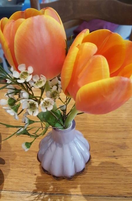 Blumenschmuck. Zwei rot-gelbe Tulpen in einer kleinen Vase auf dem Tisch.