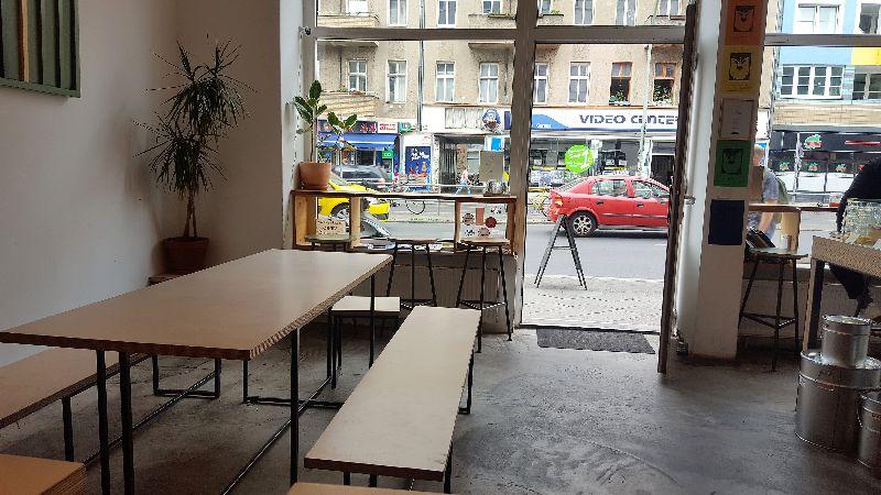 Isla Coffee vorderer Bereich. Tische und Bänke. Weiße Wände. Große Fenster.