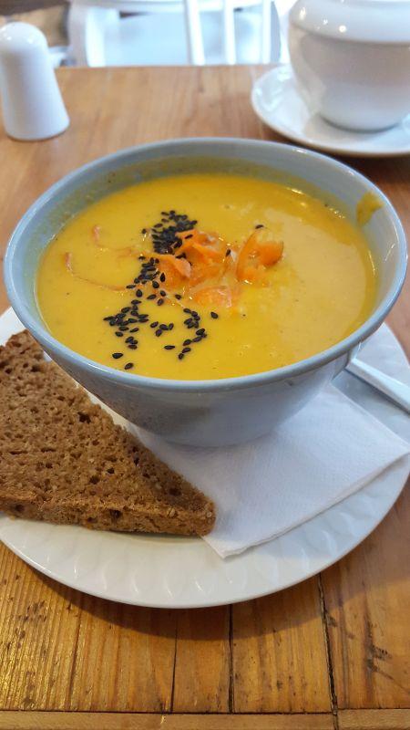 Café con amore. Erdnuss-Möhren-Suppe in einer Schale und mit schwarzem Sesam und Karottenabrieb garniert.