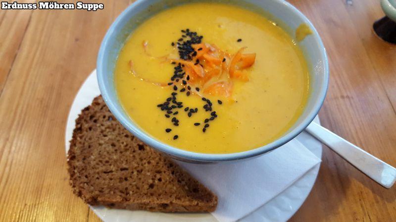 Erdnuss-Möhren-Suppe. Kleine Portion in einer Schüssel, verziert mit schwarzen Sesam und Karottenabrieb, dazu ein Stück Vollkornbrot.