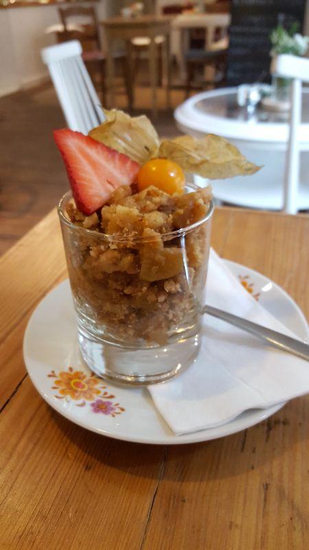 Café con amore. Apple crumble warm in einem Glas serviert und mit einer halben Erdbeere und Physalis garniert.