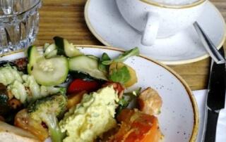 Frühstück Special Berlin. Community Frühstück. Frühstücksteller, Kaffeetasse und Wasserglas.