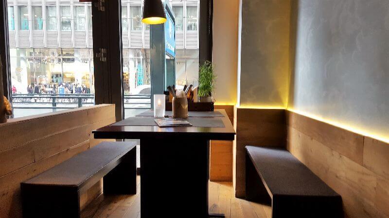 Peter Pane Interieur. Dunkle Holzbänke und Tische. Hängeleuchte und indirekte Beleuchtung.