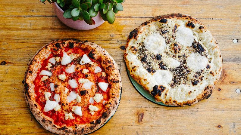 Proof's Place Pizza Pop Up. Holztisch mit zwei Pizzen. Pizza Margherita und Pizza Smoky.