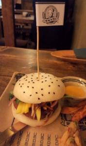 Buddha Burger bestehend aus Bao-Brötchen, Seitanpatty, Mango-Coleslaw, Koriander, Sojareduktion und Aiolicreme, dazu Süßkartoffelstäbchen und Kimchi.