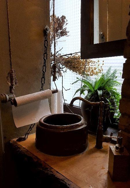 Umami Toilette. Waschbecken rund aus Stein. Patinierter Messingwasserhahn. Auf Seilen hängt eine Papierrolle zum Hände trocknen. Ein paar Pflanzen.