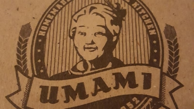 Umami Logo. Umamischriftzug in geschwungener Banderole, dahinter da Abbild einer älteren asiatischen Dame. Umami logo. Umami lettering in a curved banderole, behind it a picture of an elderly Asian lady.
