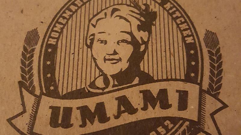 Umami Logo. Umamischriftzug in geschwungener Banderole, dahinter da Abbild einer älteren asiatischen Dame. Umami logo. Umami lettering in a curved banderole, behind it a picture of an elderly Asian lady.