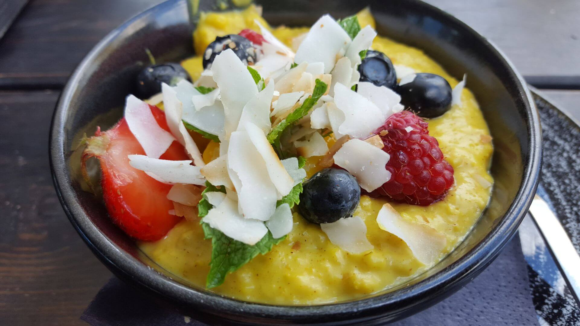 Golden Porridge with turmeric, cinnamon, mango, coconut, berries and mint.