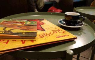 Veganer und Nichtveganer gehen in Genf essen. Kaffeetisch mit Büchern und Espressotasse.