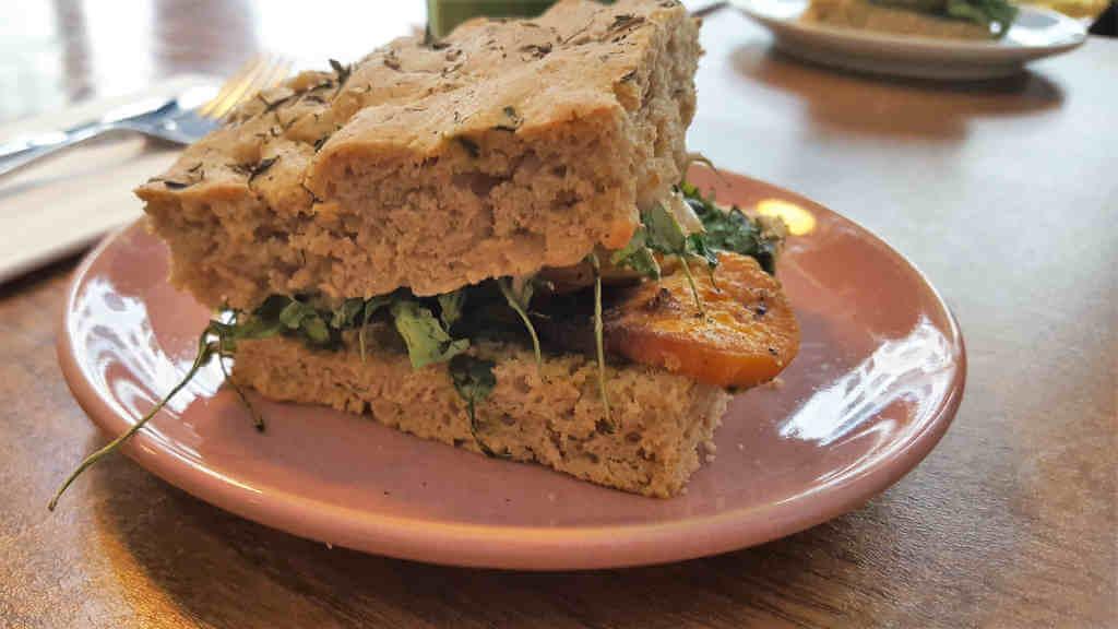Veganer und Nichtveganer gehen in Genf essen. Kräuterfoccacia mit Thymian, Tomate, Süßkartoffel etc.