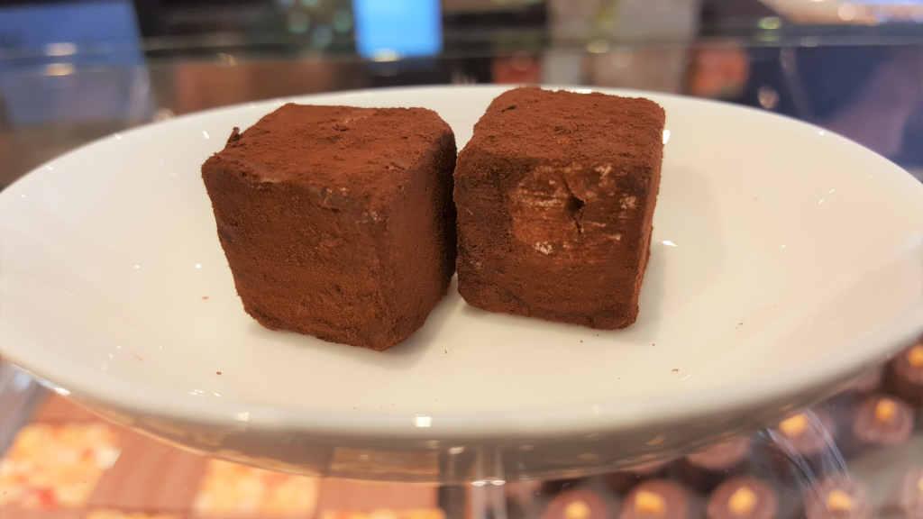 Veganer und Nichtveganer gehen in Genf essen. 2 Sprüngli Noisettewürfel auf einem Teller.