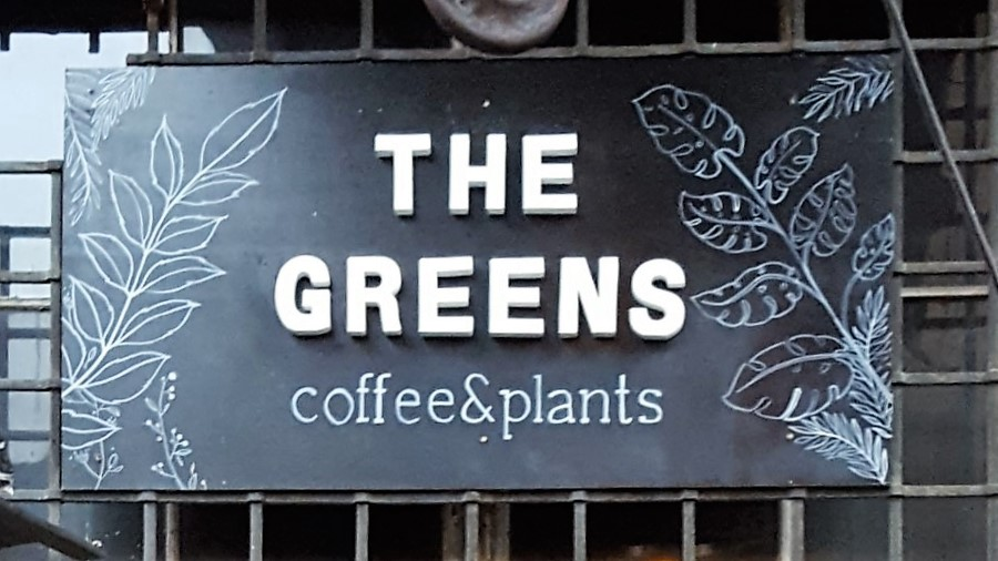"""Breakfast Special Berlin. The Greens Schild über dem Eingang. Display above the entrance saying """"The Greens coffee & plants""""."""