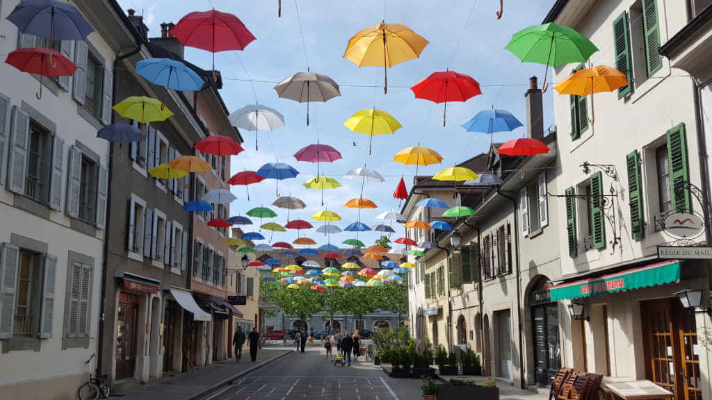 Carouge art installation with colorful umbrellas above the street.