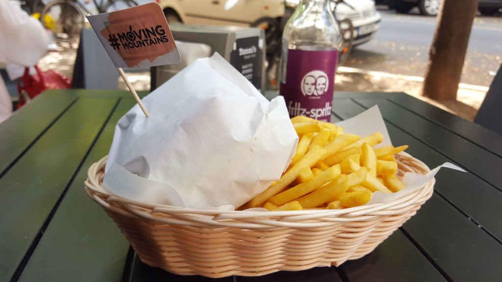Tommi's Burger Joint. Burger in Papier gewickelt mit Pommes im Körbchen.